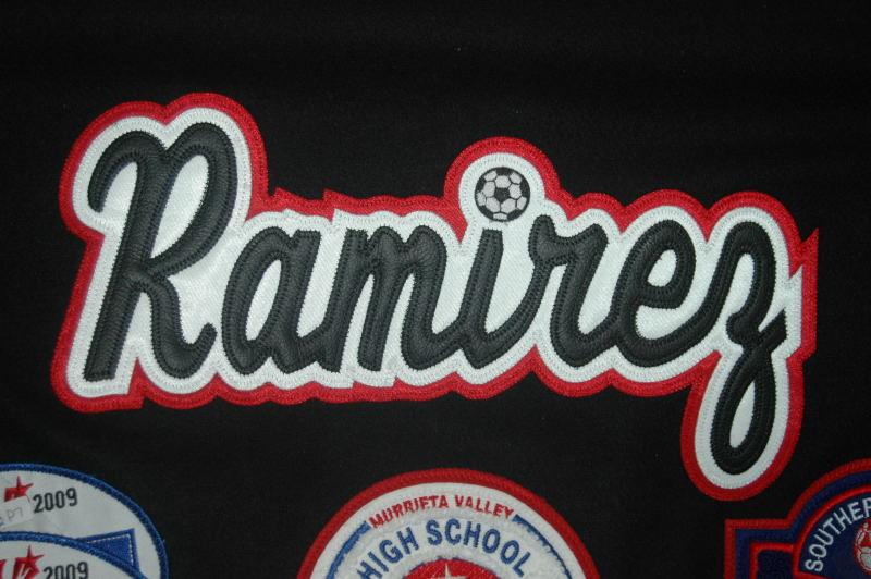 "Leather last name with custom soccer ball dotting the ""i""."